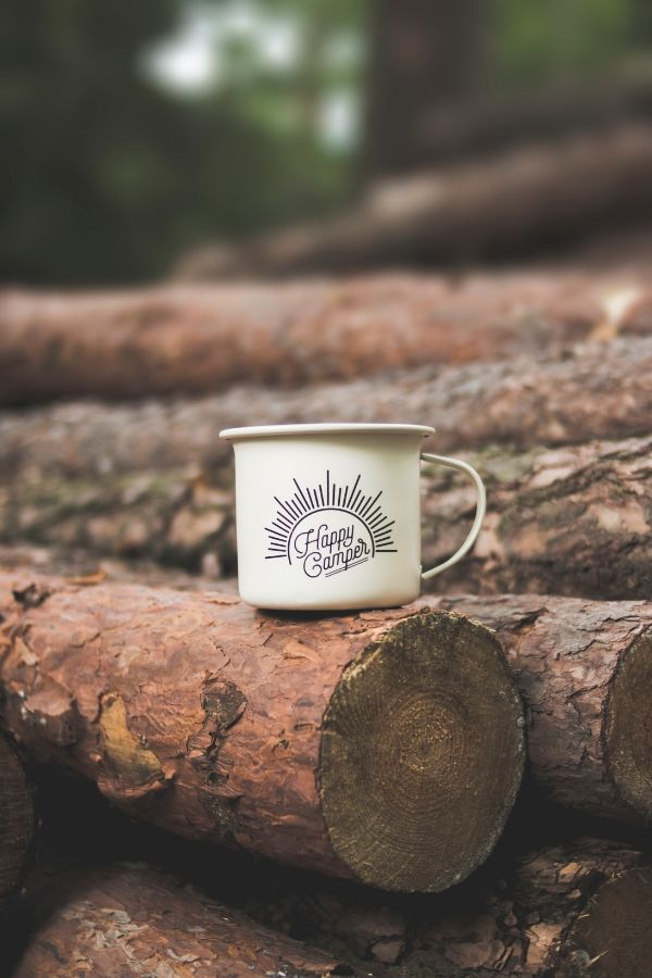 happy camper cup sitting on wood