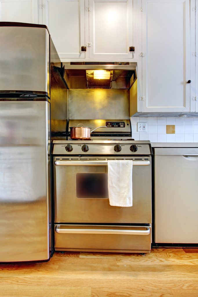 Stove and refrigerator in stainless steal with white kitchen and hardwood floor.